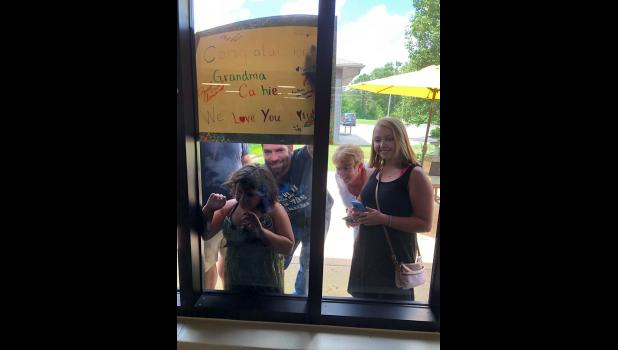 Kathie Lewis's family support their contestant through the windows. (submitted)